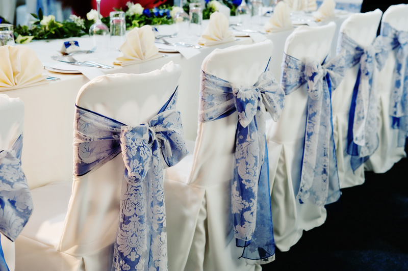 Stunning venue dressing - blue sash bow with lace on pristine white chair cover