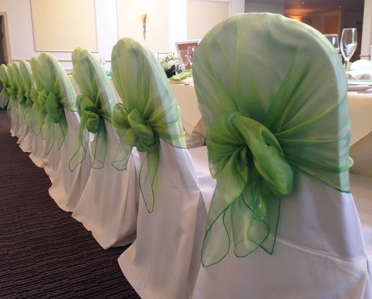 Green chiffon circular bow with white cotton chair covers