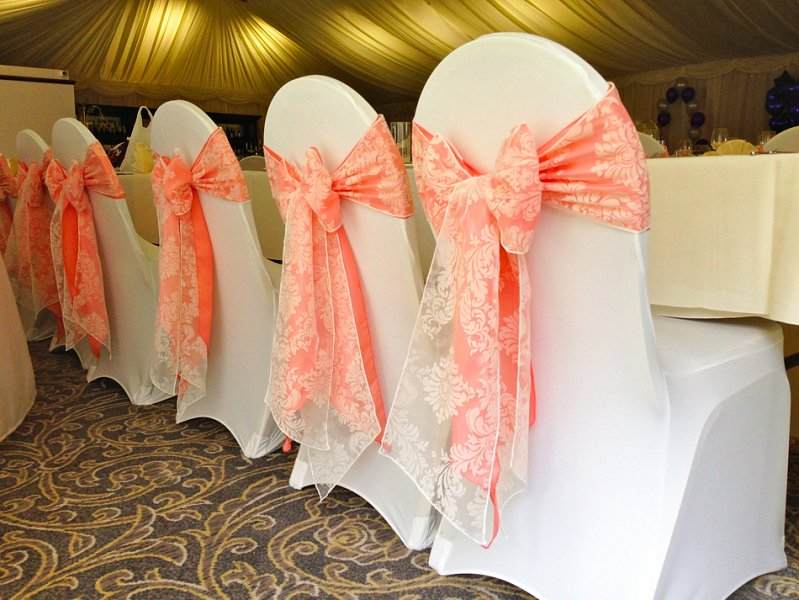 Peach satin and white lace sash bows with white stretch lycra chair covers