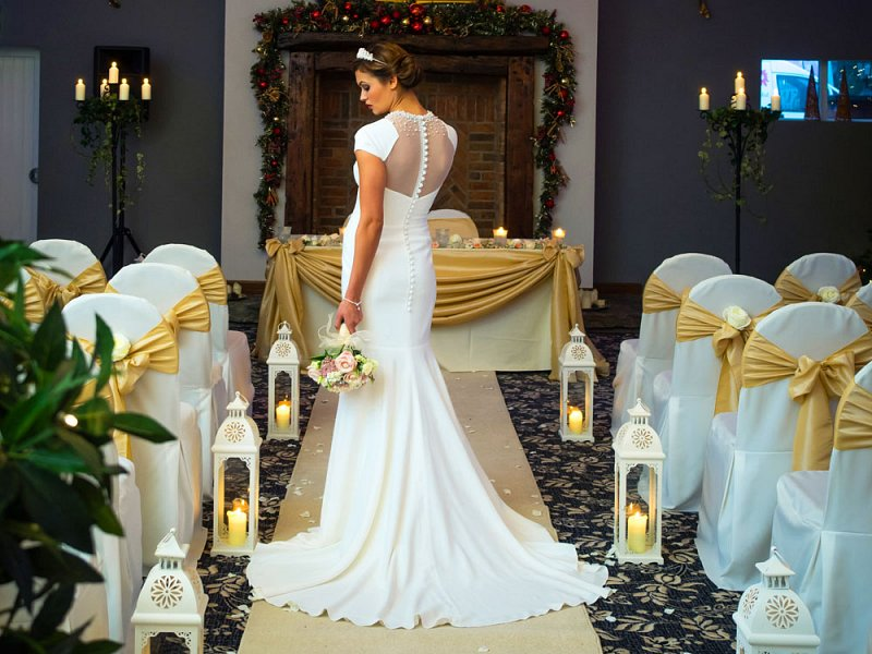 White chair covers, opulent gold sash bows & ambient lanterns by Sophisticated Events