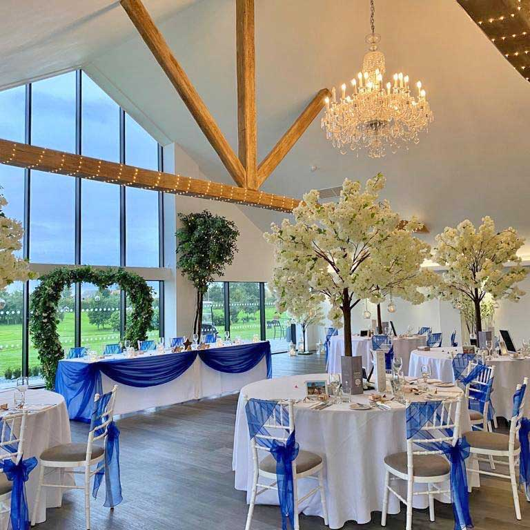 Blossom trees & blue theme venue styling by Sophisticated Events at Staining Lodge Glass House