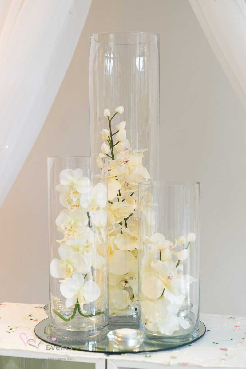 Large 3 cylinder vase display with ivory phileanopsis in water with floating candles