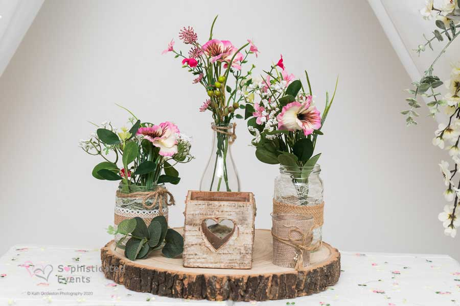 Centrepiece log slice with hessian milk bottle jars & rustic heart box display