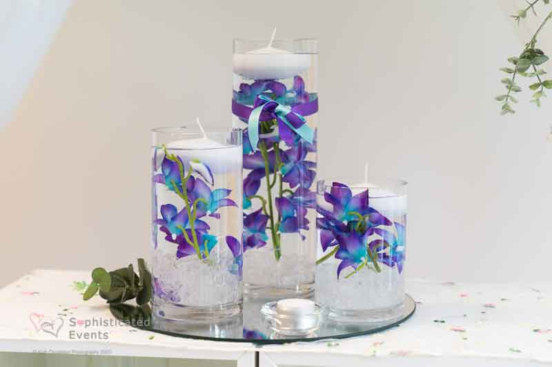 Small 3 cylinder vase display with blue phileanopsis, glass stones & in water with candles