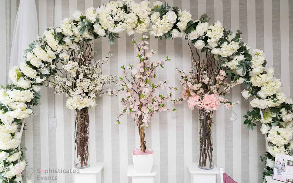 Ivory & green circular floral hoop with twig displays & blush blossom tree on white pedestals - wedding decorations y Sophisticated Events