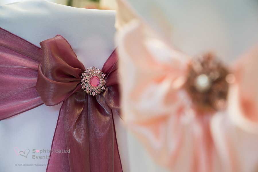 Chair cover bows - mulberry sash with beautiful brooch accessory - Sophisticated Events weddings styling