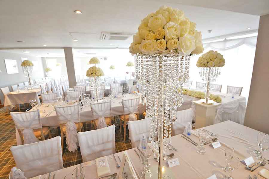 Pristine white ruffled chair hoods & chandellier table centrepieces - wedding styling & venue dressing by Sophisticated Events
