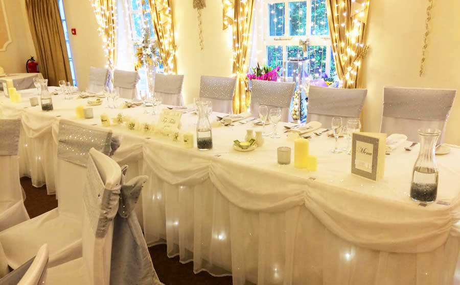 Twinkling fairylight top table swag & silver grey sash bows by Sophisticated Events at Singleton Lodge