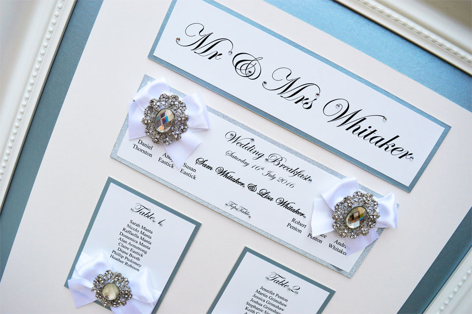 Ice blue framed wedding table plan with white bow decoration
