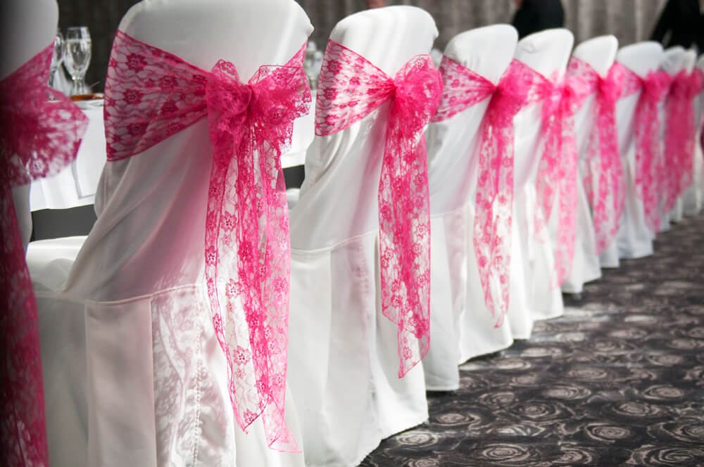 Hot pink sash bows with lace over white chair covers