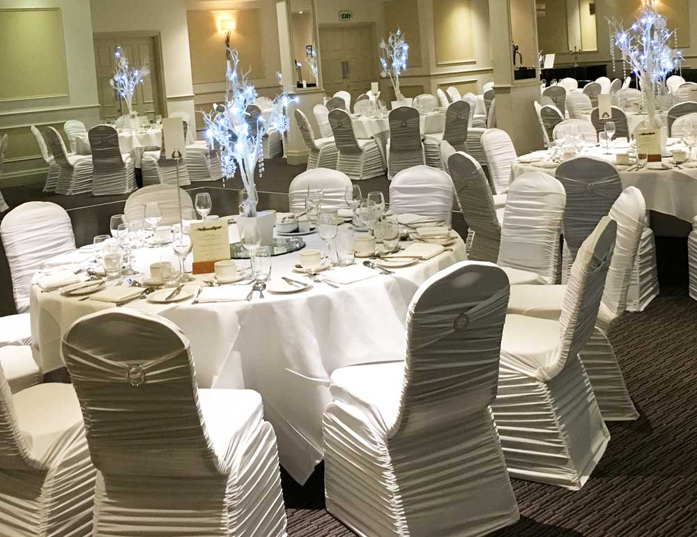 Ruched white stretch lycra chair covers with white sash and diamante brooch