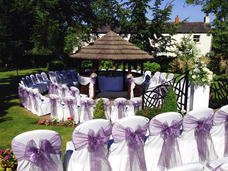 Shimmering purple sash bows & ceremony table dressed by Sophisticated Events at Ribby Hall summerhouse