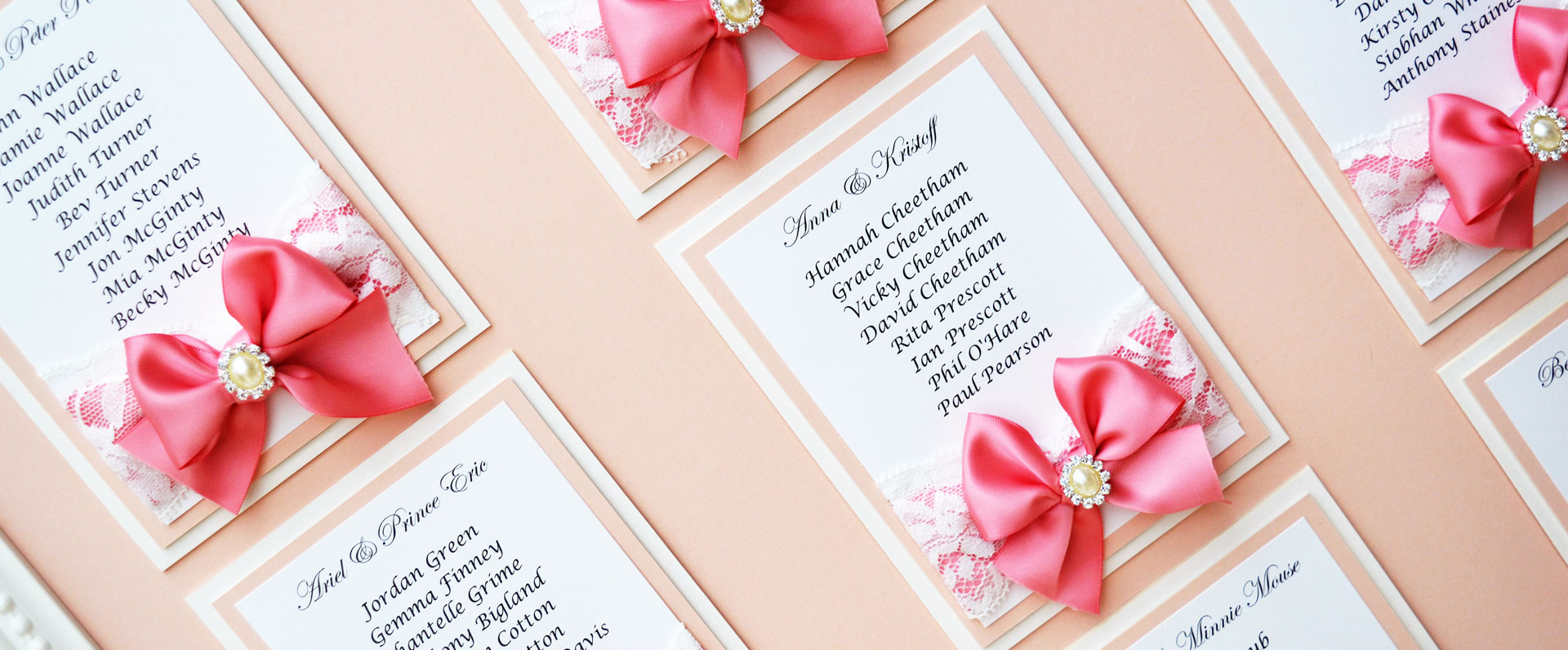 Framed pink satin bow on white lace wedding table plan