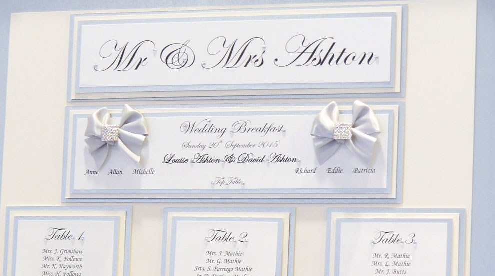 Table plan with white satin bows & silver sparkle decoration