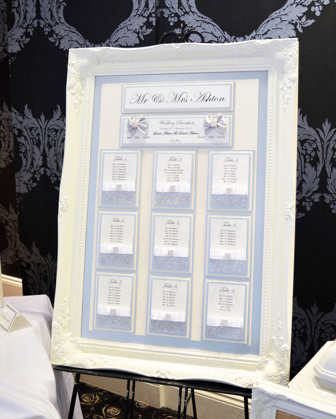 White Victoria framed table plan with white satin bows & silver sparkle decoration