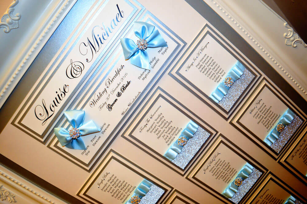 Sparkly silver table plan with satin sky blue bows