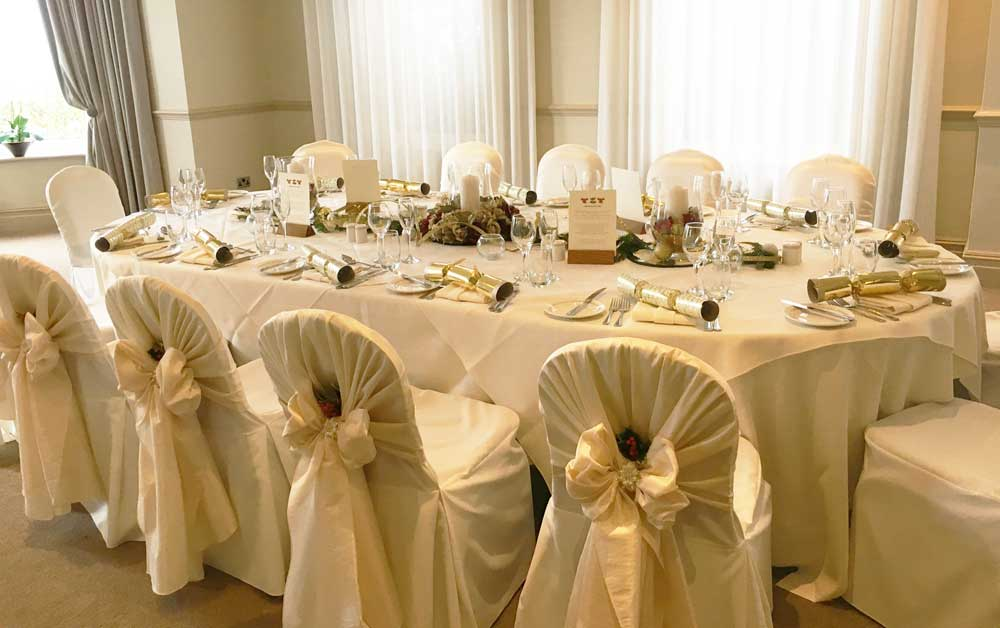 Christmas holly & berries decoration - taffeta hood over white chair covers by Sophisticated Events