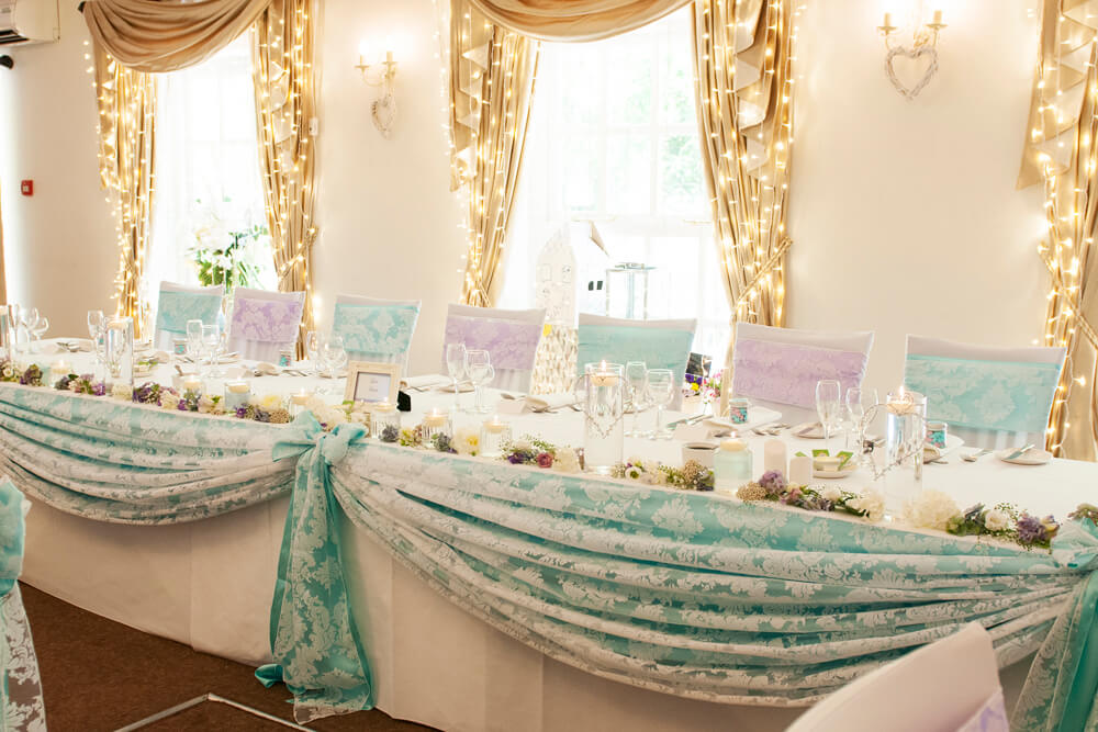 Teal & lilac wedding top table swag with white lace overlay and matching chair sash bows