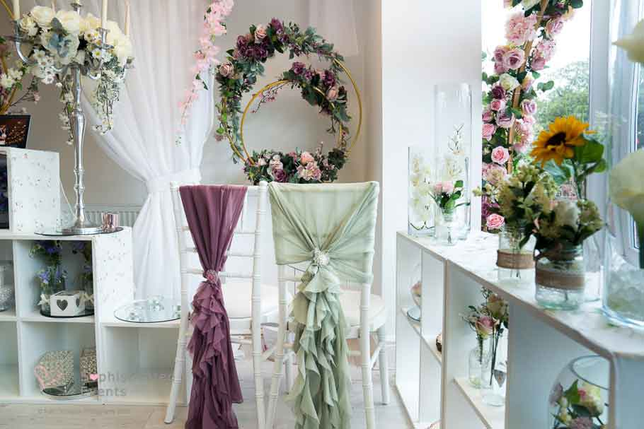 Weddings by Alexander & Co boutique displaying mauve ruffled vertical drop chair styling & sage green ruffled hood chair cover with brooch - Sophisticated Events